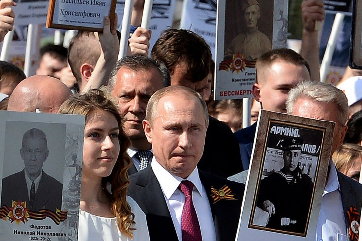 Putin holds a portrait of his fatheronthe
