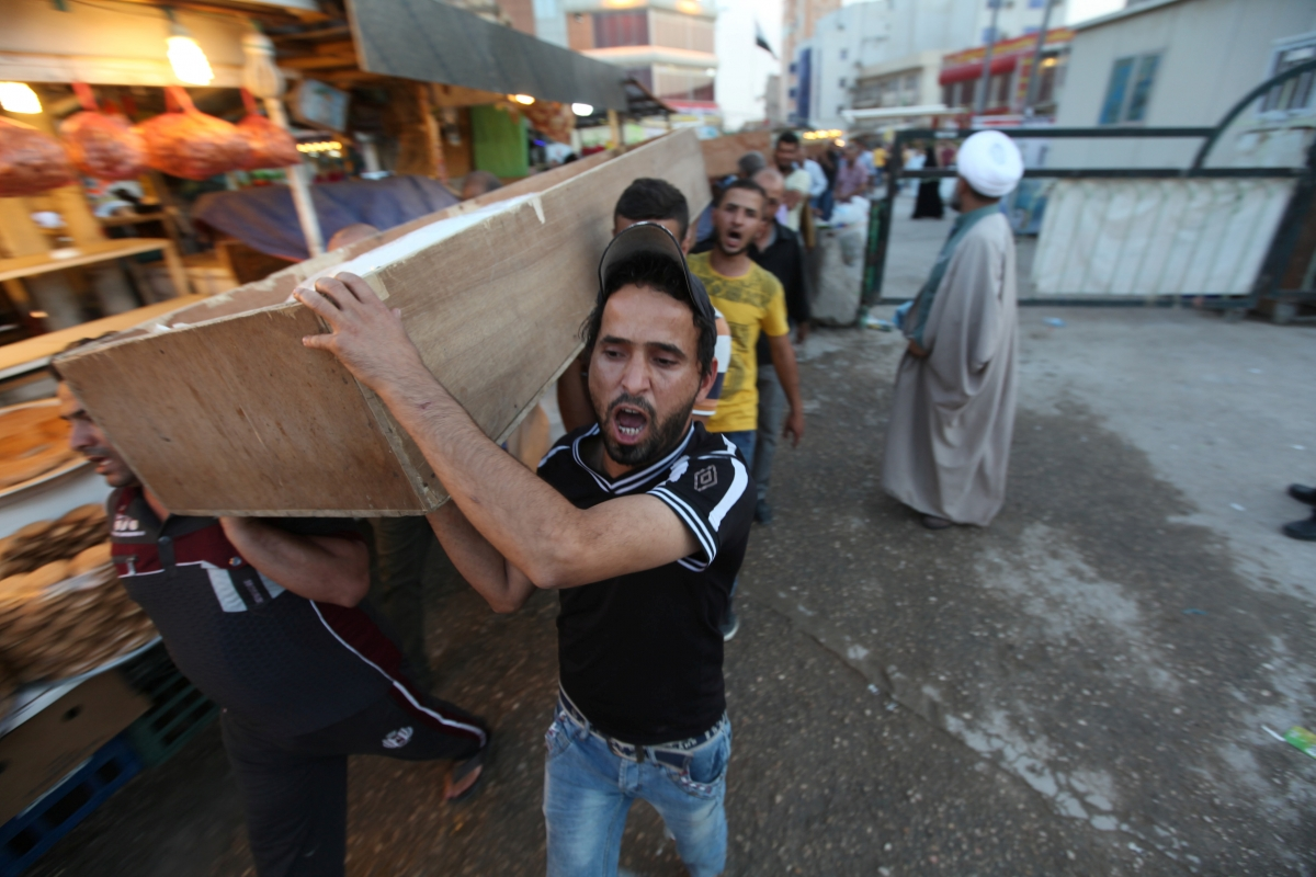 Mourners carry the coffin of their relative