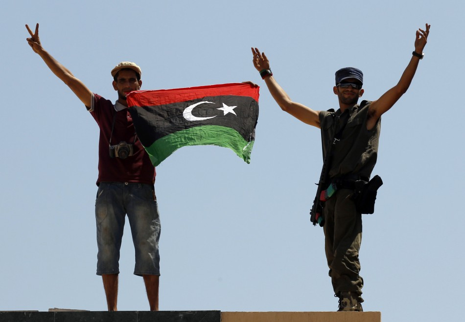 Rebel fighters show victory signs as they hold a Kingdom of Libya flag at the Tunisan border post of Ras Jdir