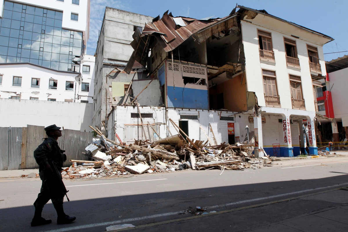 A military member walks in front of a damaged structure