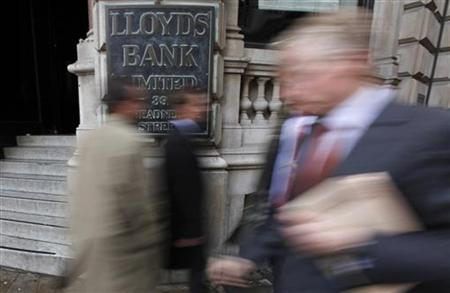 Pedestrians walk past a branch of Lloyds Bank in the City of London