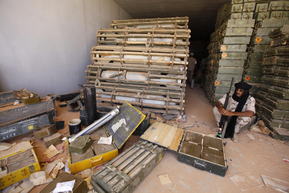 Libyan rebel fighter sits near stockpiles of ordnance inside a Gaddafi ammunition bunker