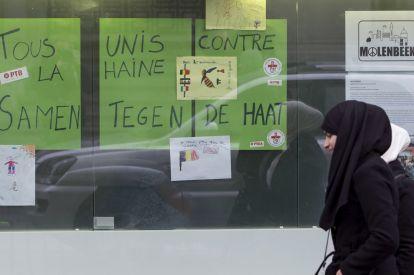 Women walk past a placard reading