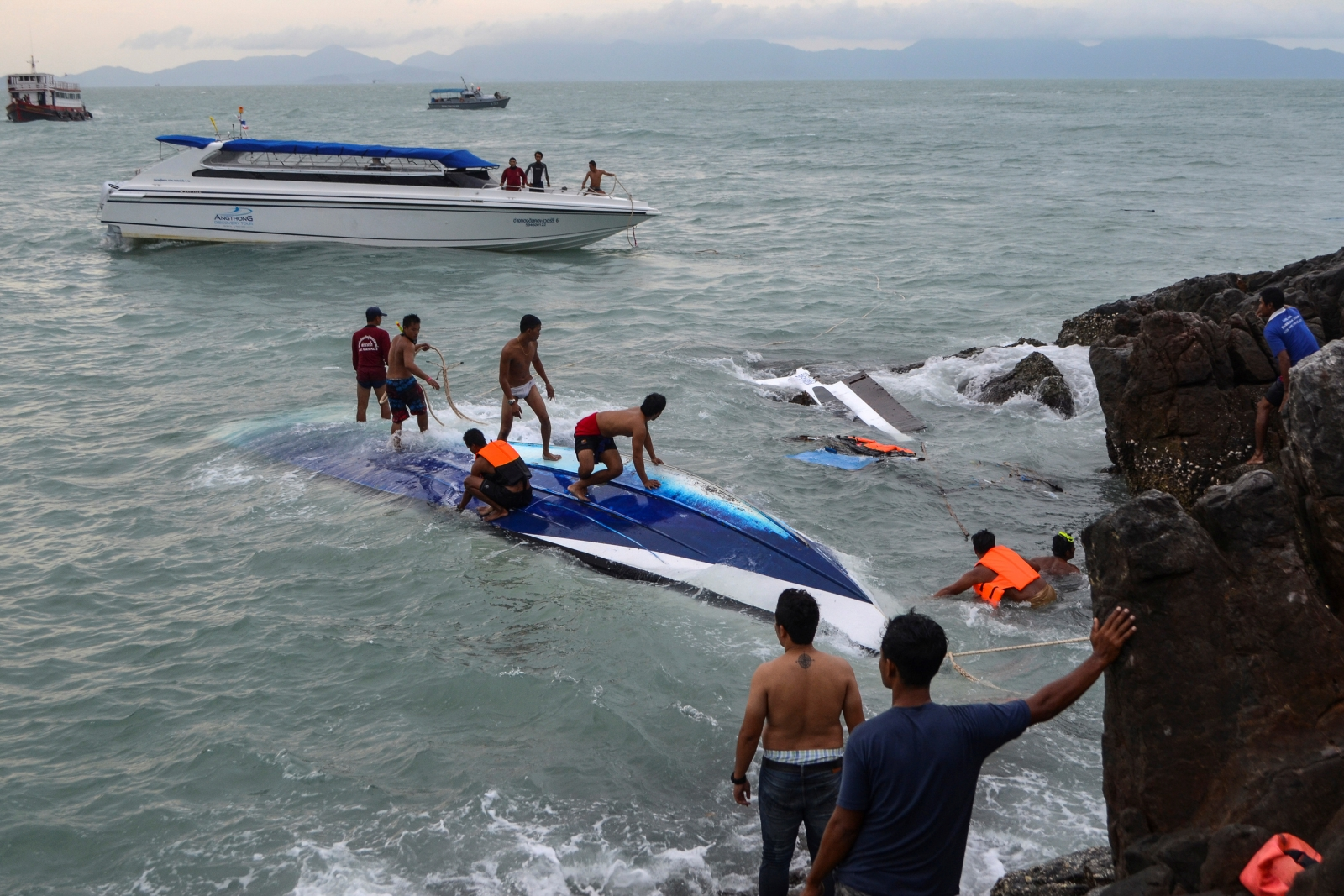 Rescue workers search for victims after a speedboat crashed