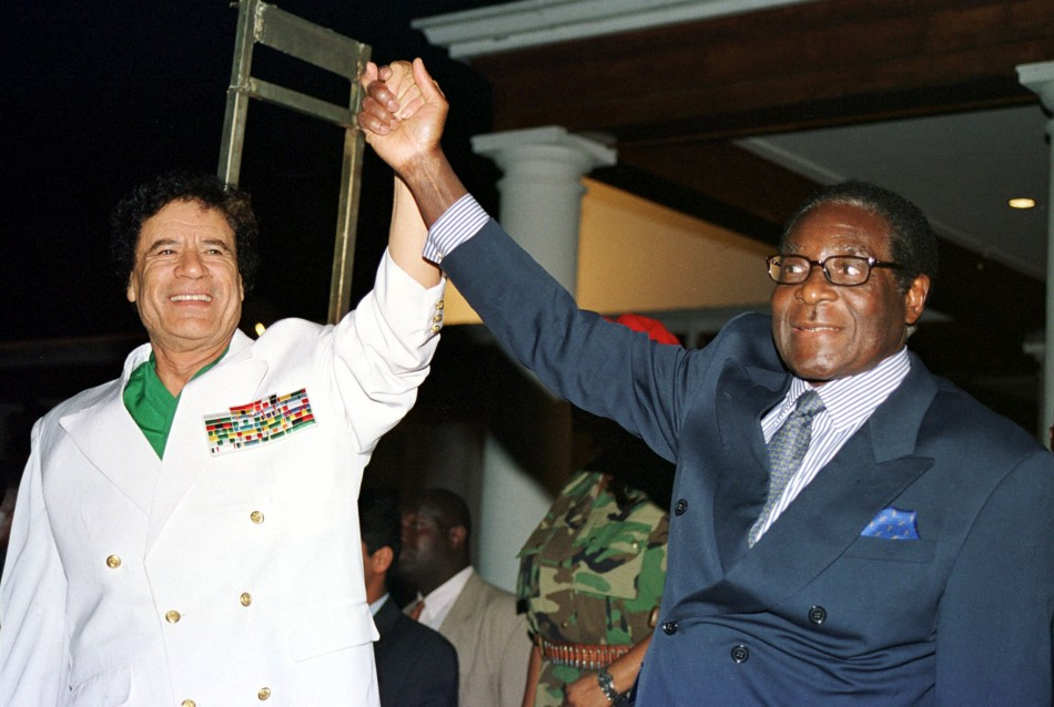 Libyan leader Colonel Muammar Gadaffi L and Zimbabwe President Robert Mugabe greet supporters outside State House in Harare July 12, 2001.