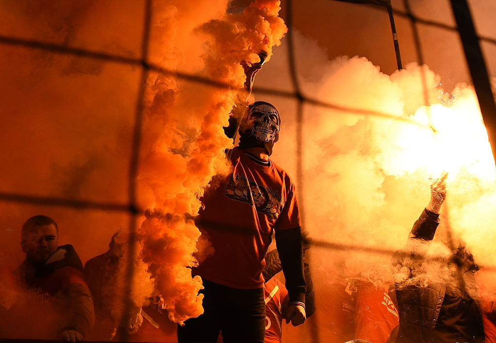 A Spartak Moscow fan lights a flare