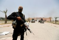 Iraqi security forces walk with their weapons at Fallujah hospital