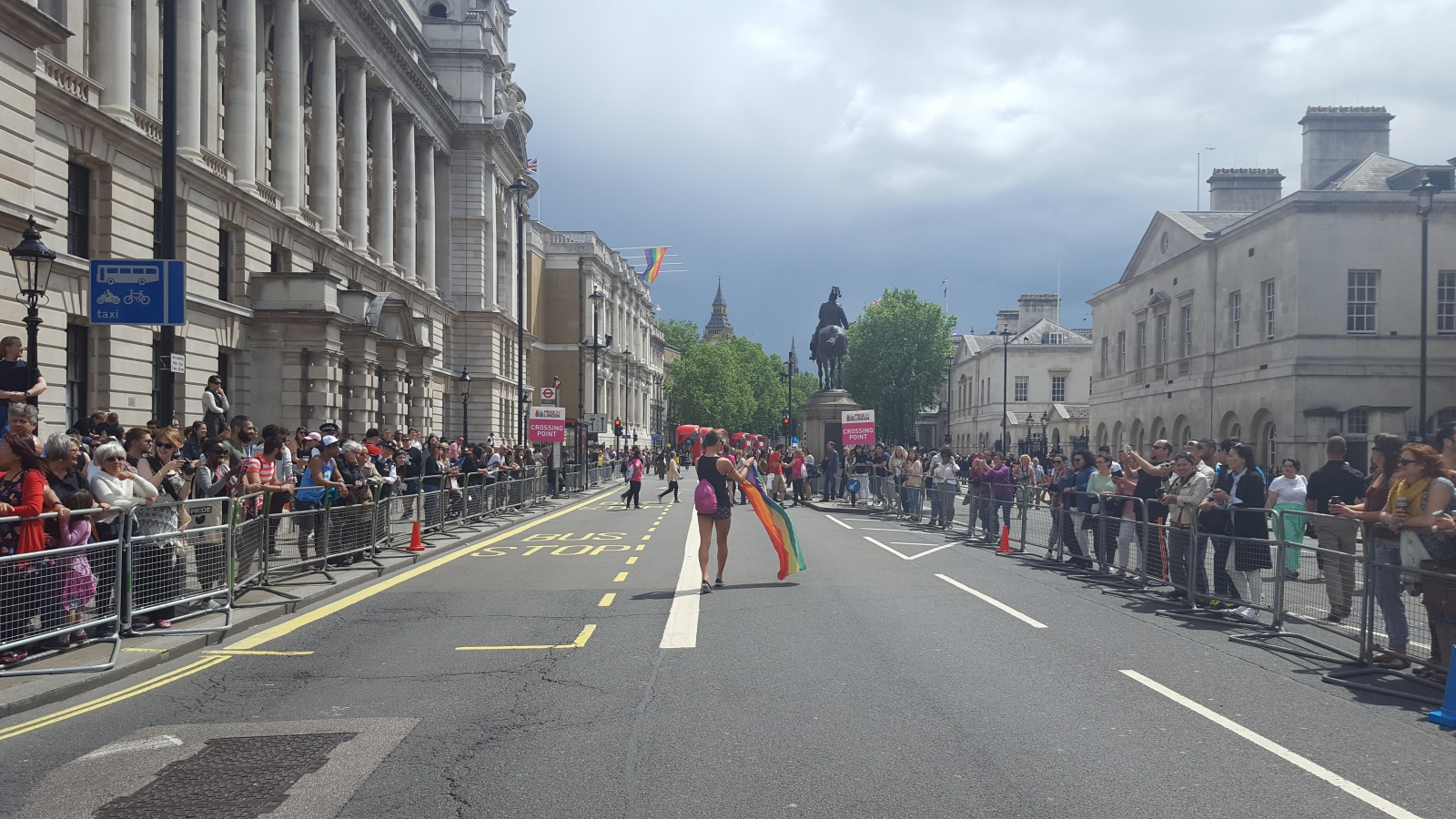 Man with rainbow flag walks down Whitehall