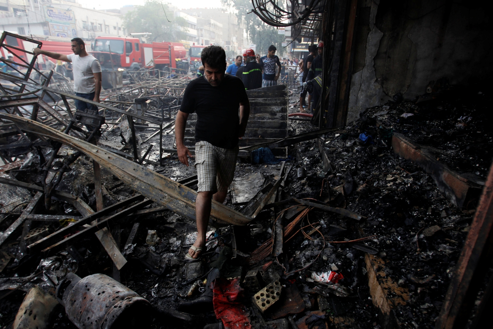 People gather at the site of a suicide car bomb in the Karrada shopping area in Baghdad