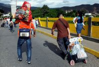 Venezuelans carrying food