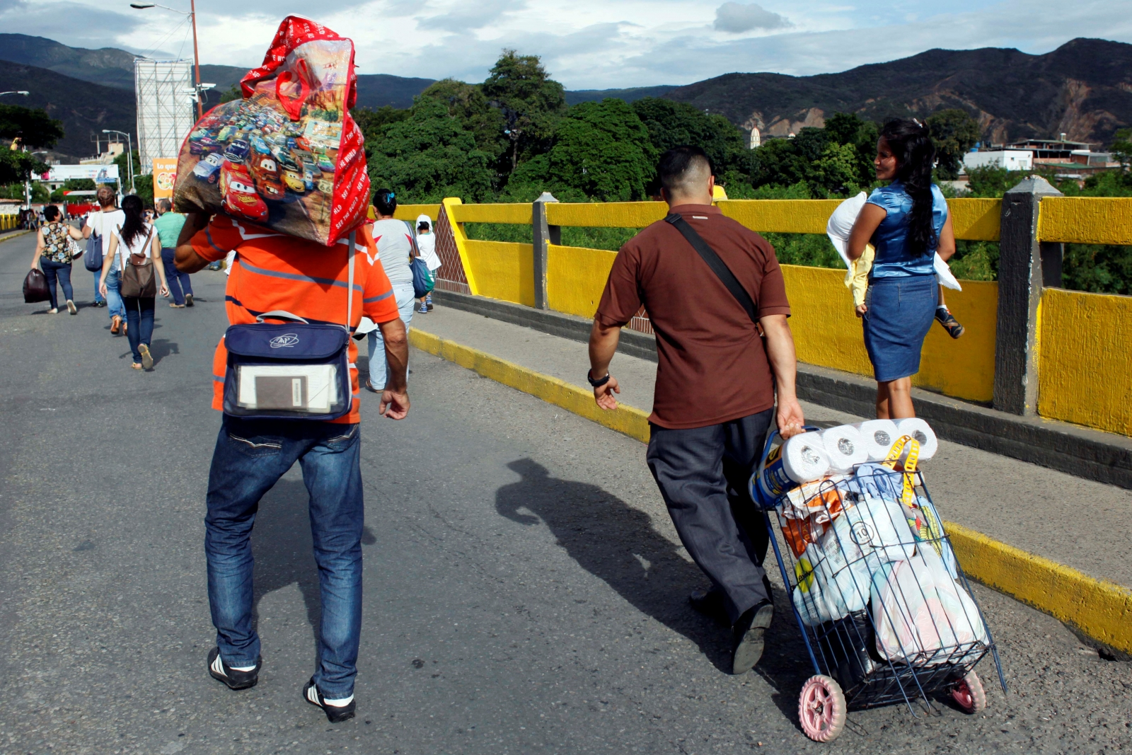 Venezuelans carrying food