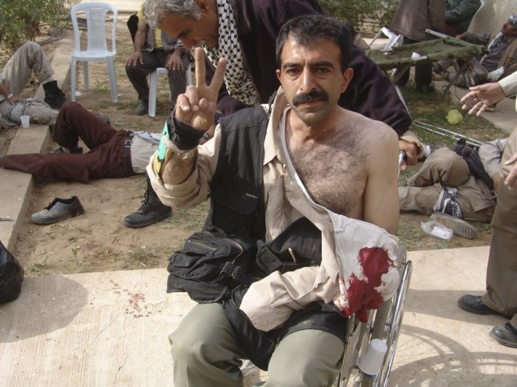 A resident gestures with a victory sign after clashes with Iraqi security forces at Camp Ashraf,