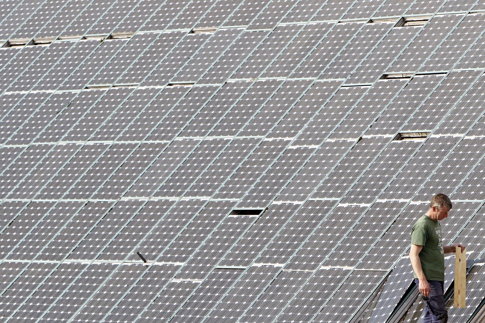A man works on solar panels