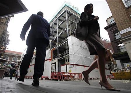 Pedestians walk past a building under construction in central London