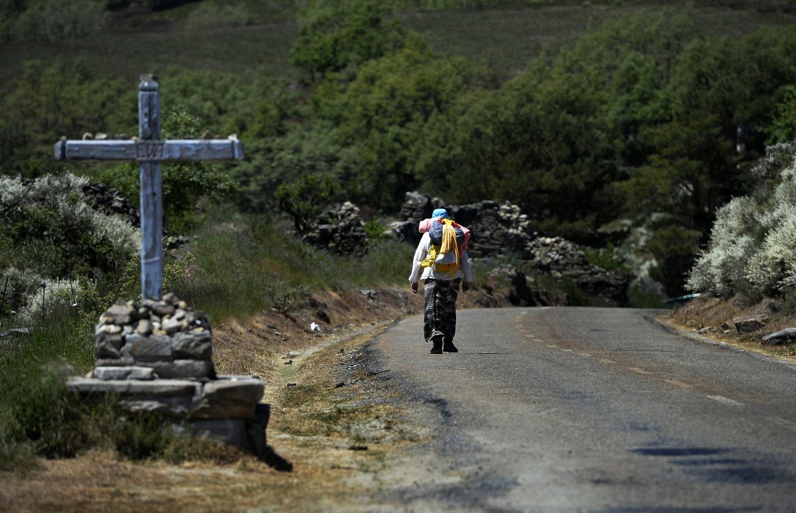 A pilgrim walks toward Santiago de Compostela