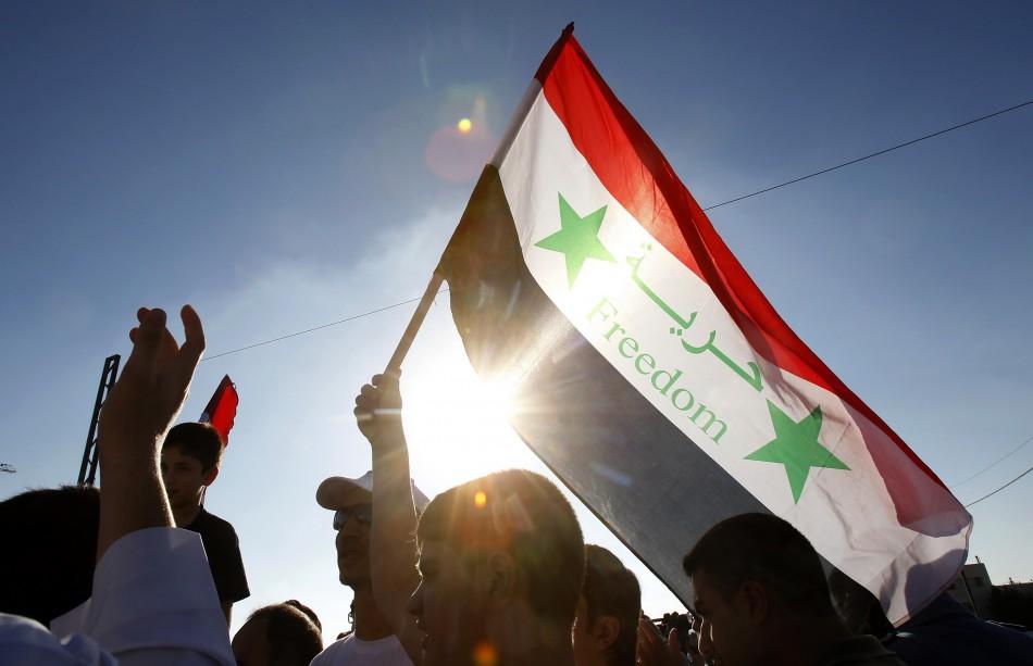 Syrians living in Jordan shout slogans against Syrian President Bashar al-Assad after morning prayers on the first day of Eid Al-Fitr outside the Syrian embassy in Amman