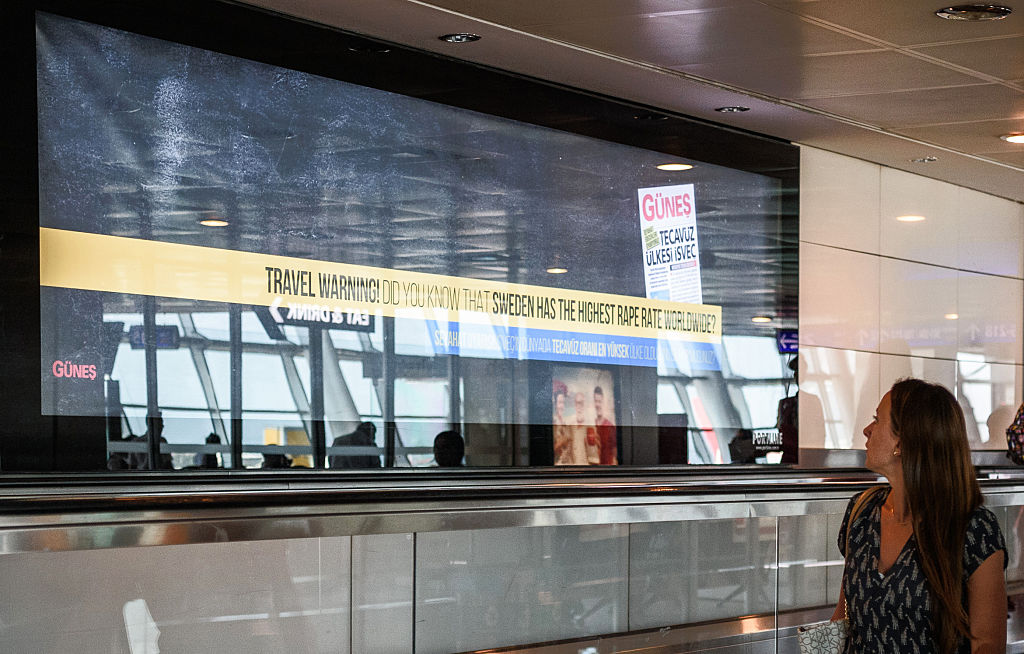 A passenger walks past a billboard advertisement reading 'Travel warning - Do you know that Sweden has the highest rape rate worldwide?'