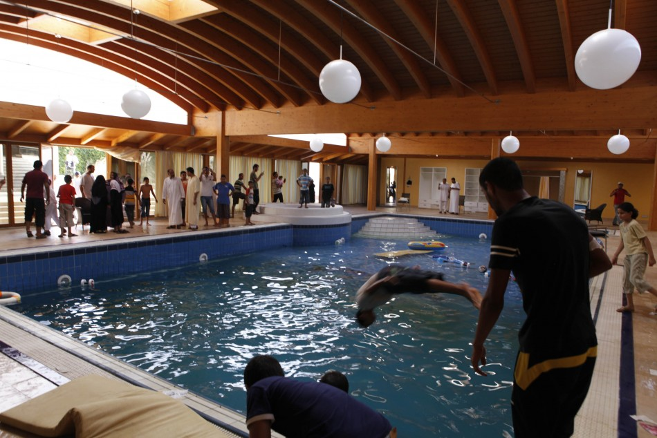 A boy jumps into a swimming pool at Aisha Gadhafi's compound in Bin Ashour district in Tripoli August 26, 2011. Aisha Gaddafi is the daughter of Libyan leader Muammar Gaddafi.