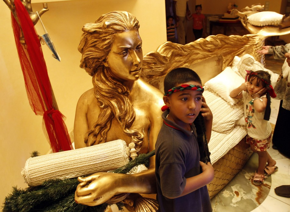 A boy stands next to a golden sofa with a statue of Aisha, the daughter of Libyan leader Muammar Gadhafi inside her house in Tripoli August 26, 2011