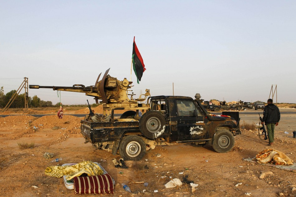 An anti-Gaddafi fighter walks next to a vehicle as he mans the last checkpoint to enter Bani Walid, currently held by pro-Gaddafi forces, in south east Tripoli