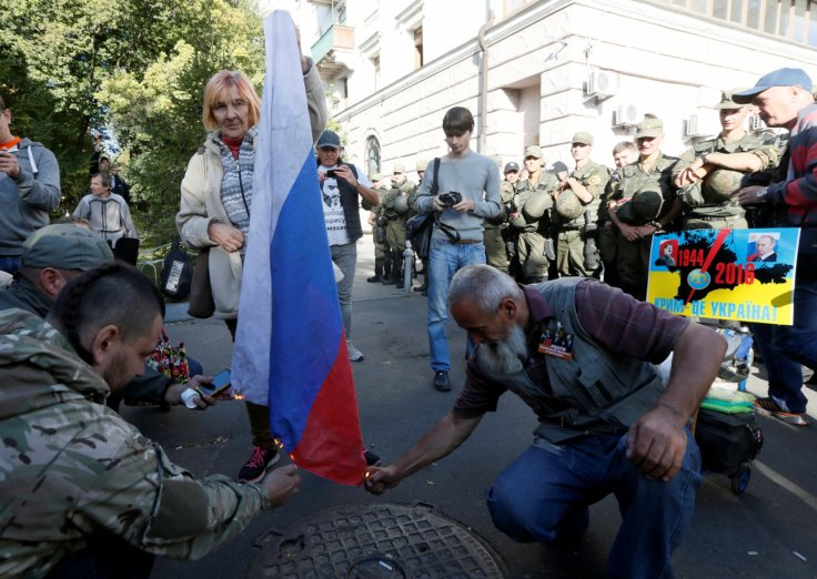 Protesters burn a Russian flag