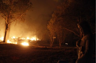 A religious figurine is illuminated by wildfires burning out of control near Bastrop