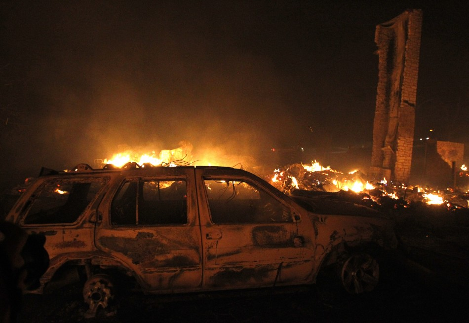 A burnt car sits in front of a house that has been razed to the ground as a wildfire burns out of control near Bastrop