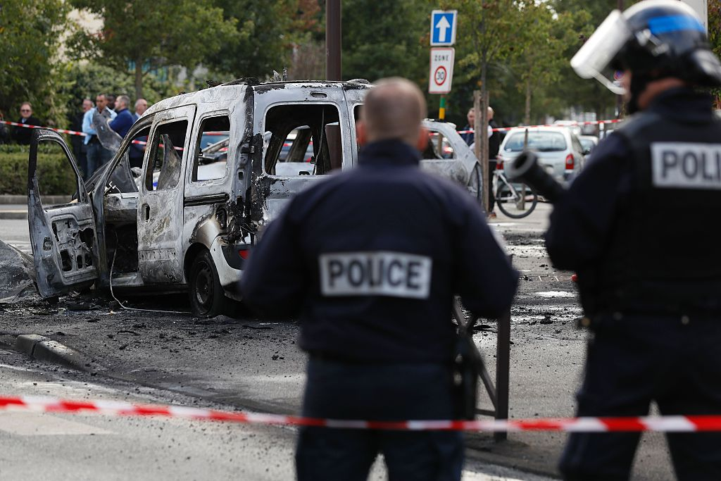 Police stand guard near a burned police vehicle (back) and a van in Viry-Chatillon