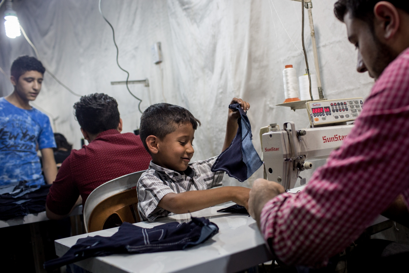Syrian refugee children in Turkey making clothes for UK