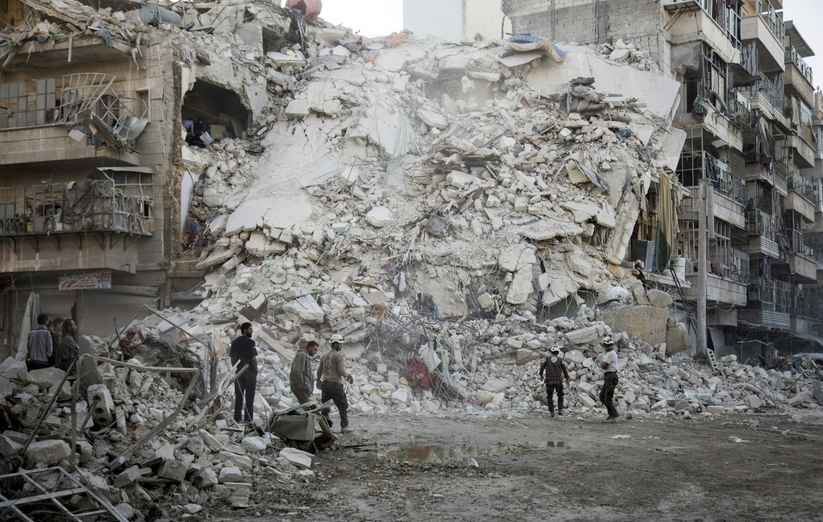 the White Helmets search for victims amid the rubble of a destroyed building