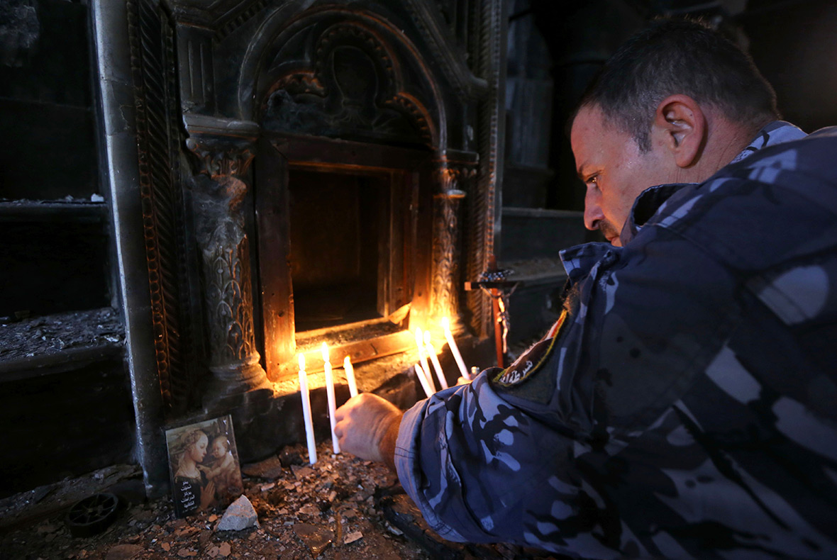 Image result for An Iraqi Christian forces member lights a candle at the Church of the Immaculate Conception on October 30, 2016, photos