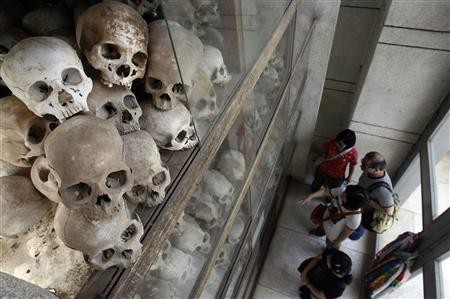 Tourists look at skulls on display at the memorial stupa filled with more than 8,000 skulls of victims of the Khmer Rouge regime at Choeung Ek
