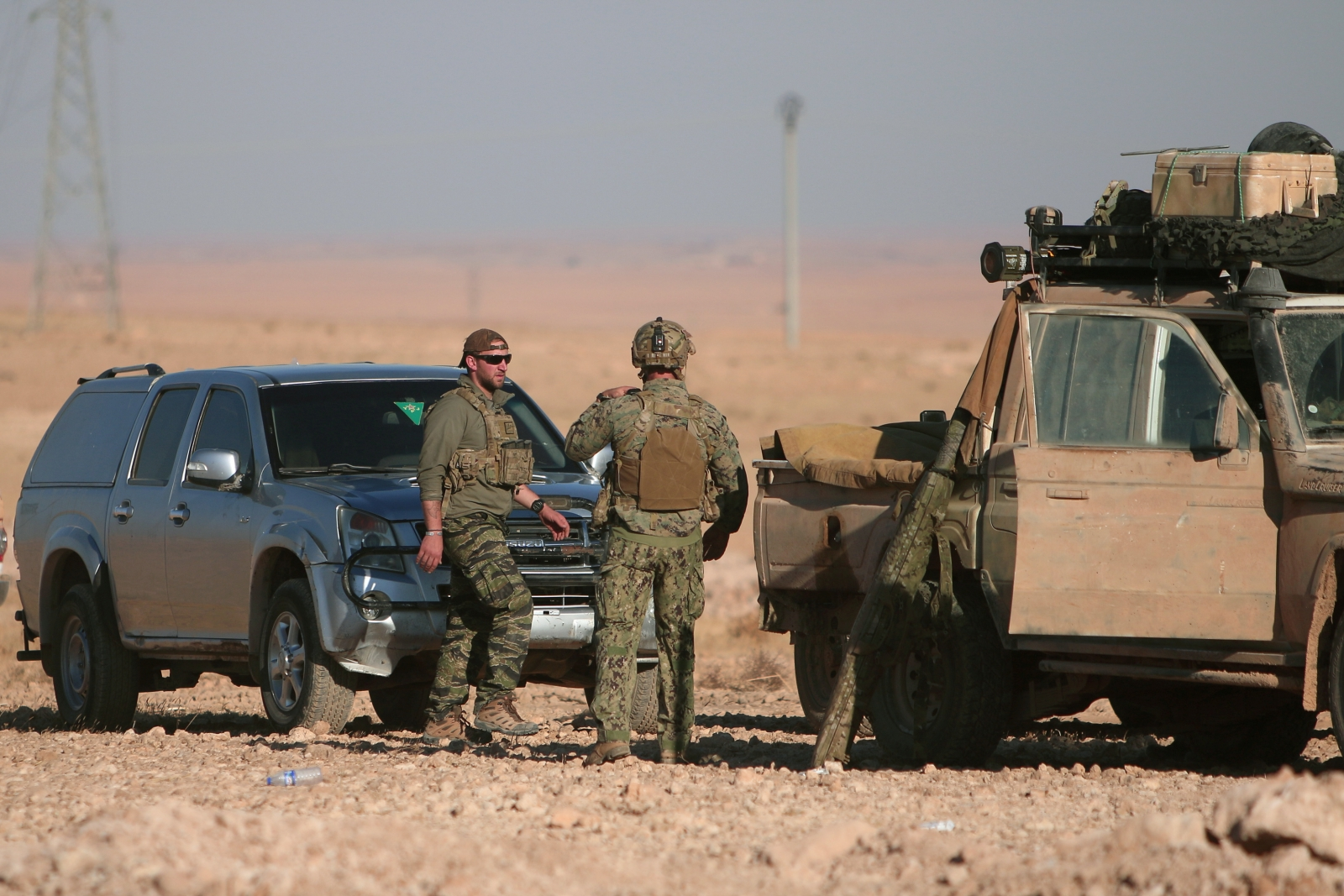 U.S. fighters stand near military vehicles