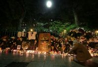 A man lights a candle at a makeshift memorial near the Bataclan concert hall