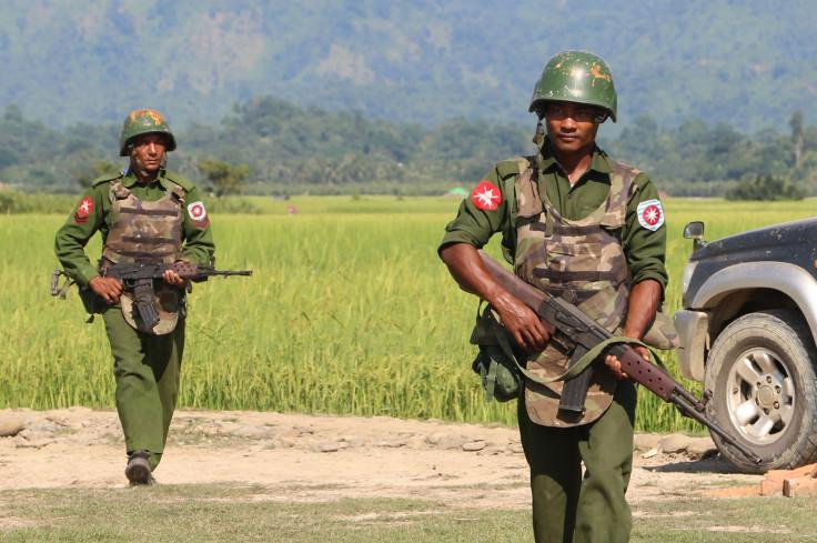 Armed Myanmar soldiers patrol a village in Maungdaw