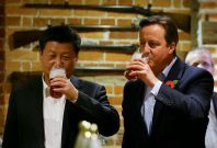 British Prime Minister David Cameron (R) drinks a pint of beer with Chinese President Xi Jinping at a pub in Princess Risborough near Chequers, northwest of London, on October 22, 2015.