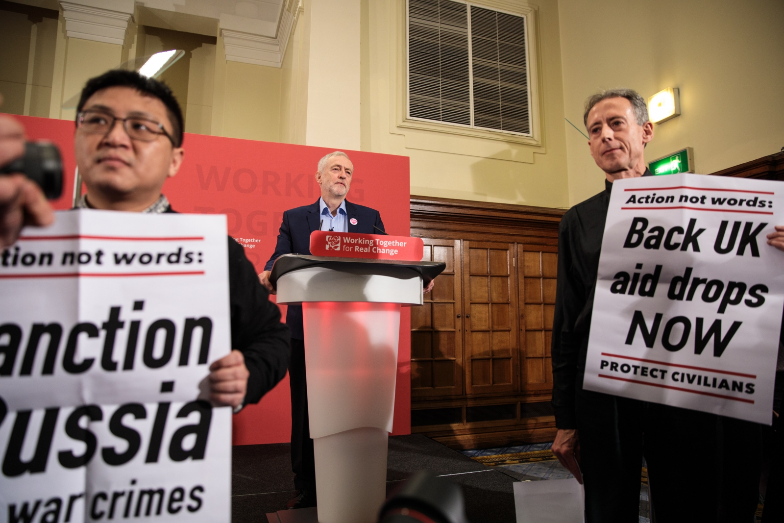 Peter Tatchell (R) stages a protest as Labour Leader Jeremy Corbyn (C) makes speech on International Human Rights Day