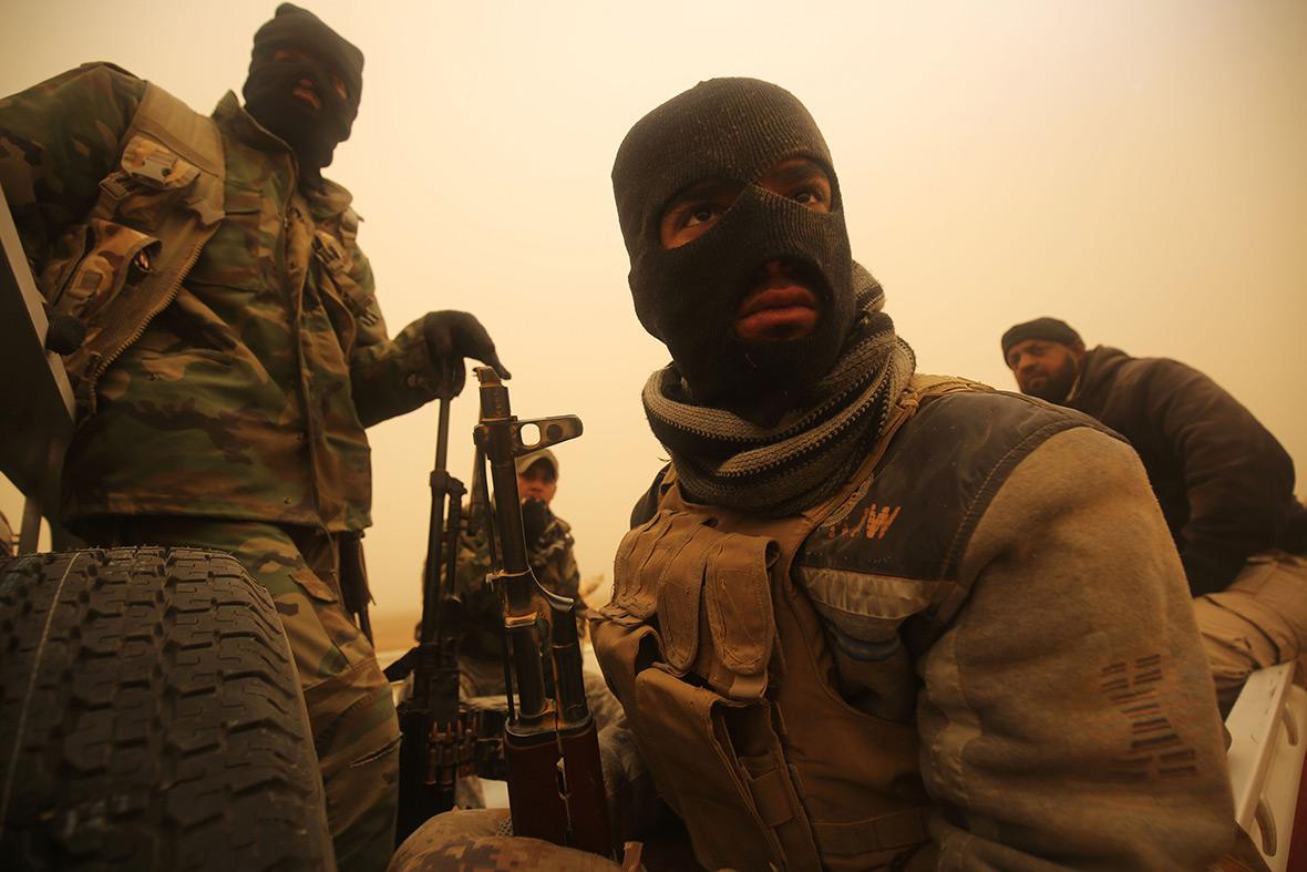 Shia fighters sit in a