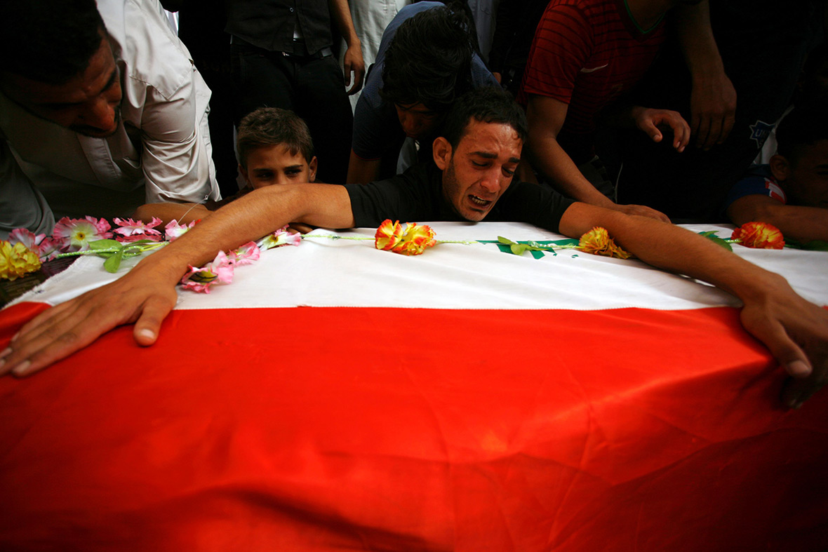Iraqis mourn over a coffin