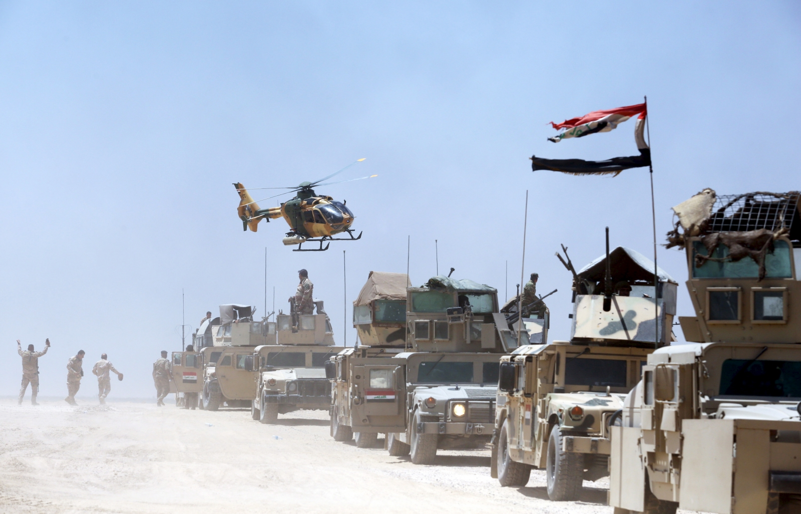 An Iraqi helicopter flies over military vehicles in Husaybah, in Anbar province