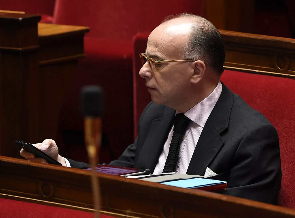 French Interior minister Bernard Cazeneuve looks at his mobile during a session of questions to the government at the National Assembly in Paris