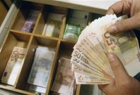 A teller counts euro banknotes inside a National Bank of Greece branch in Athens