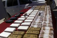 A soldier stands next to packages containing confiscated drugs during a presentation to the media in Tijuana