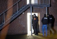 Policemen enter a home for asylum seekers in Emmerich, western Germany, on December 22, 2016.