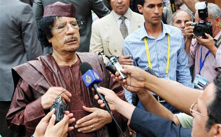 Libyan leader Gaddafi addresses the media as he leaves the venue of the AU Summit in Kampala