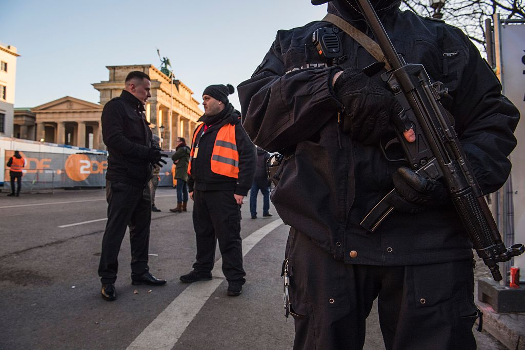 A police officer (R) and security guards (L) stand guard near the capital\'s Brandenburg Gate on December 31, 2016,