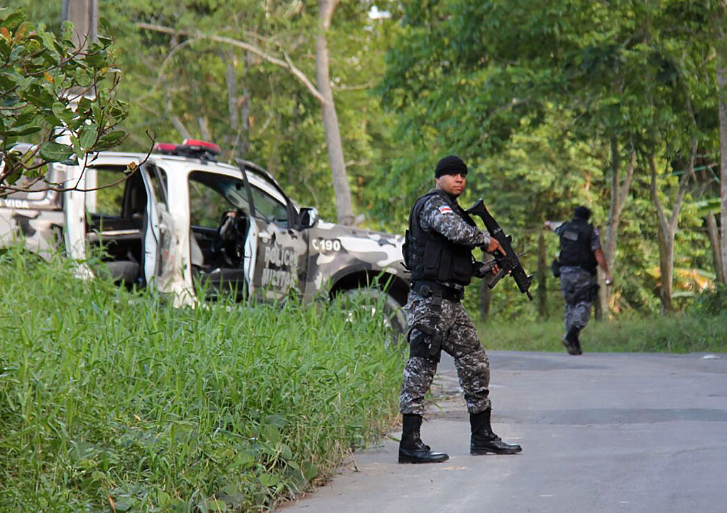 Military police officers track for fugitives of the Anisio Jobim Penitentiary Complex after a riot in the prison left at least 60 people killed and several injured,