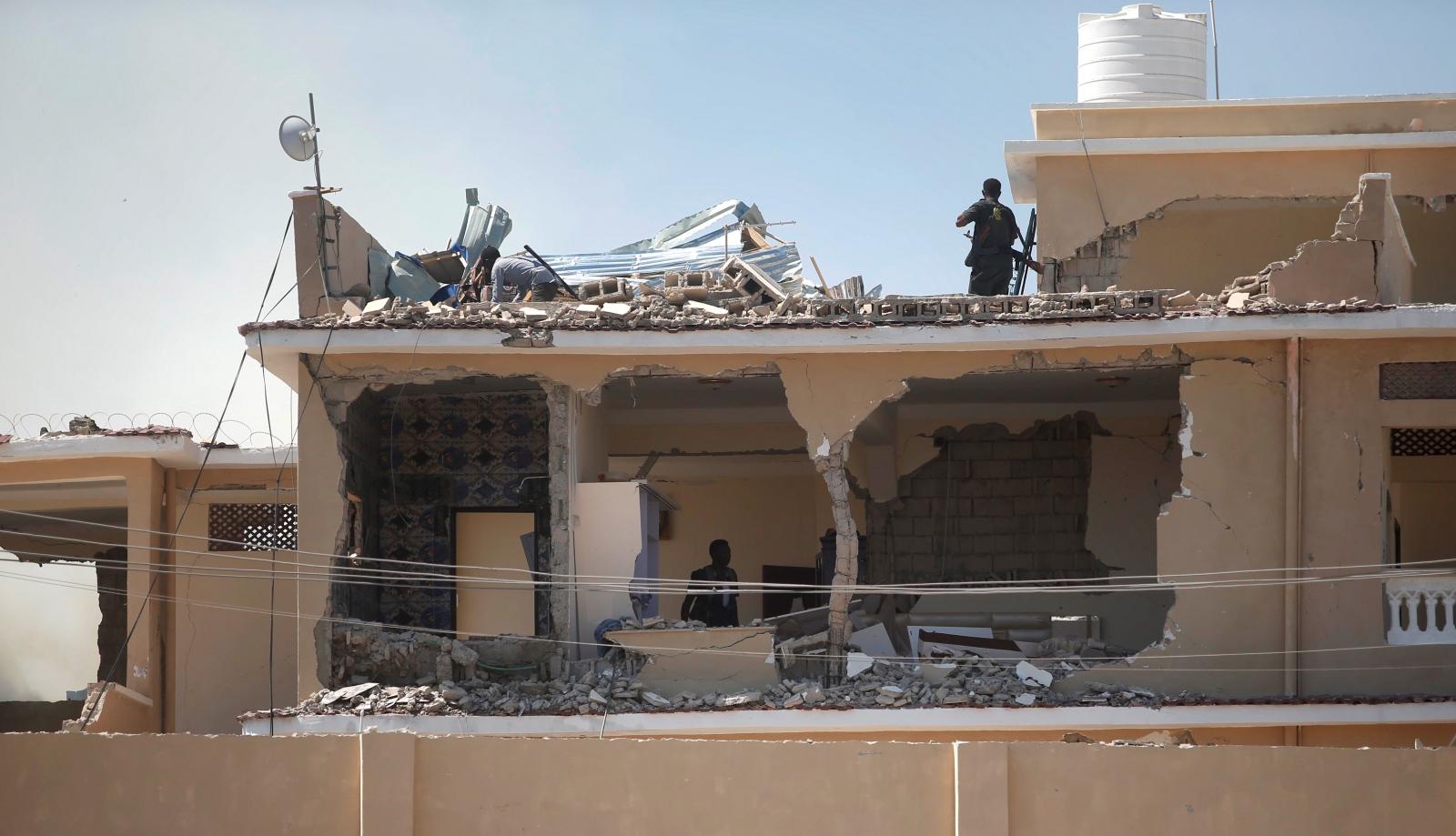 Somali policemen inspect a destroyed hotel building