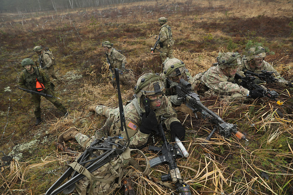 Members of the U.S. 173rd Airborne Brigade and a Lithuanian infantry soldier (L) participate in the Iron Sword multinational military exercises on November 24, 2016