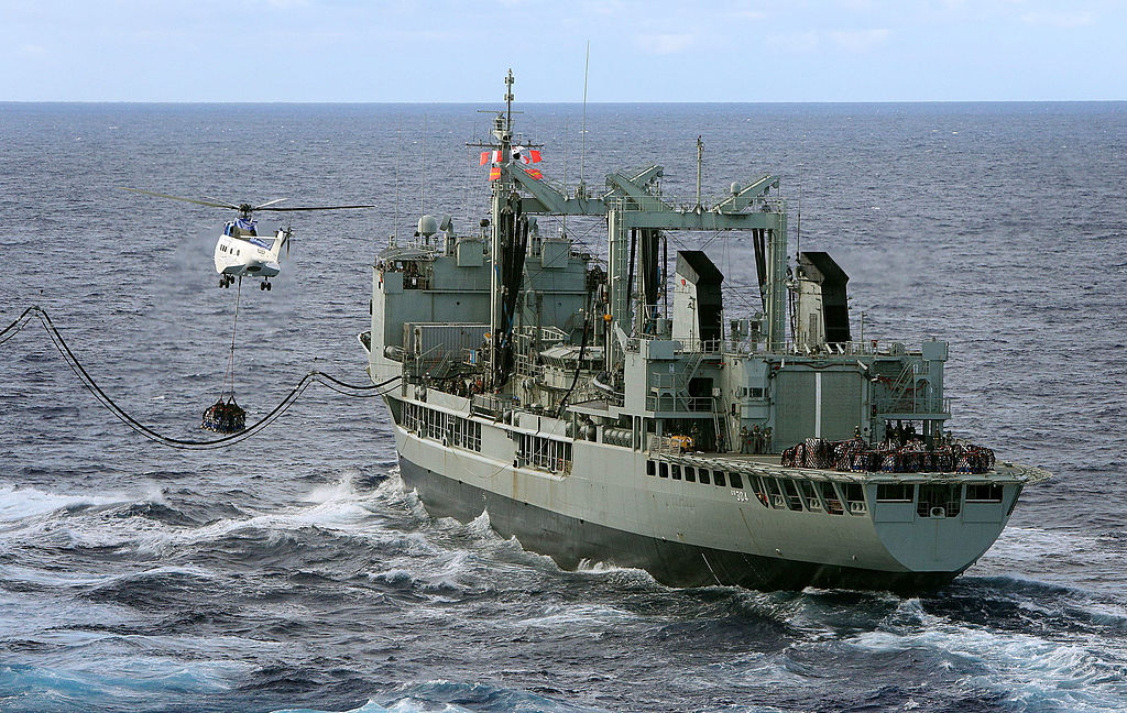 In this handout image provided by Commonwealth of Australia, Department of Defence, HMAS Success conducts a Replenishment at Sea with United States Navy Ship (USNS) Cesar Chavez, as USNS Cesar Chavez's helicopter, a Super Puma, conducts a Vertical Replen